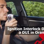 a man blowing into an ignition interlock breathalyzer in his car